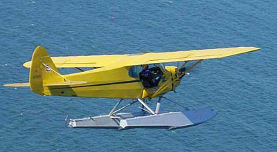 Piper Cub In flight over water